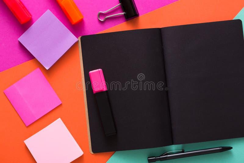 Moderner kreativer Arbeitsplatz mit stilvollem schwarzem Notizblock stockbilder