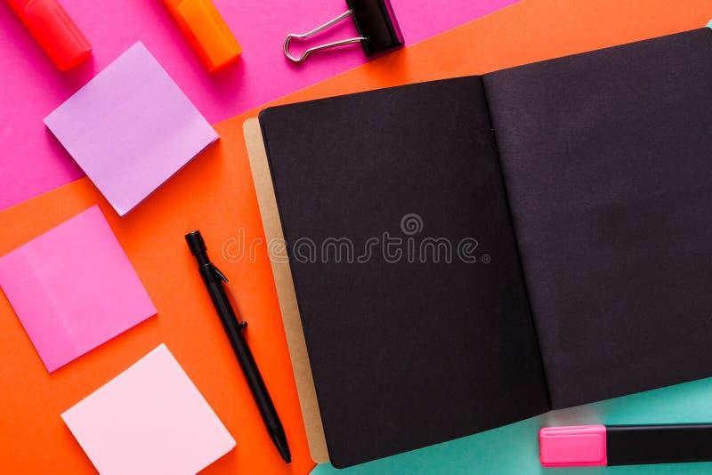Moderner kreativer Arbeitsplatz mit stilvollem schwarzem Notizblock lizenzfreie stockfotos