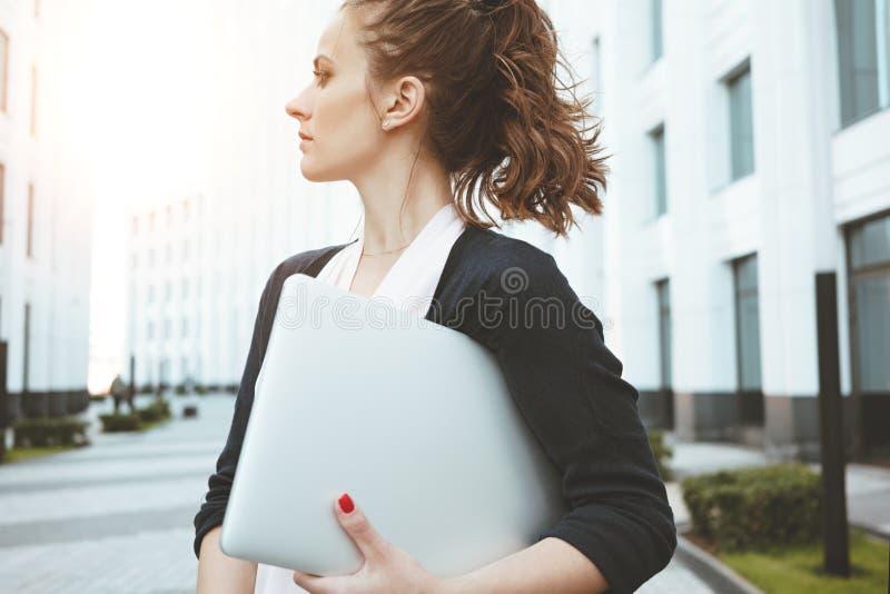 Moderner Laptop des jungen hübschen Geschäftsfrau-Griffs, der bei der Stellung in der städtischen Straße weg schaut stockfotografie