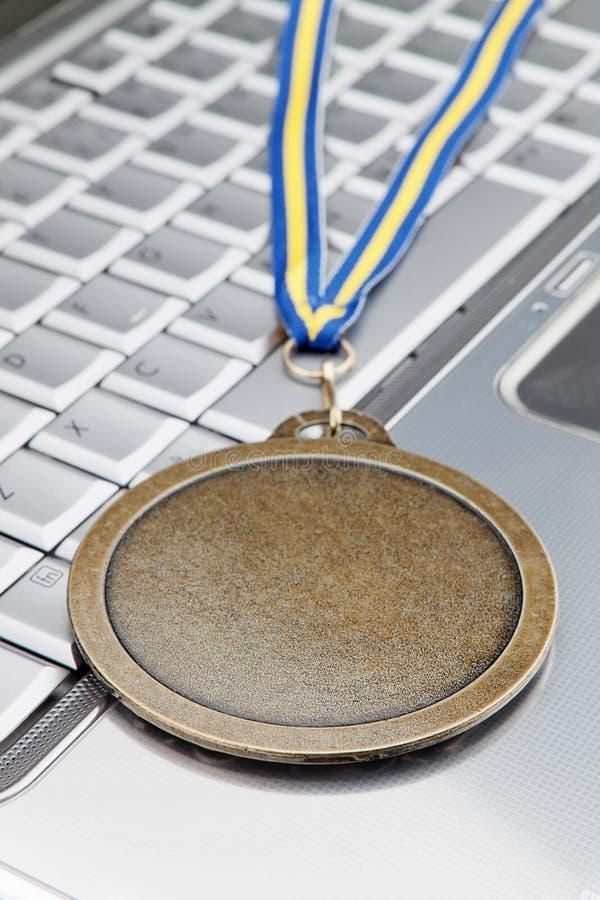 Moderner Laptop und sprechen eine Goldmedaille für Erfolg zu. stockfotografie