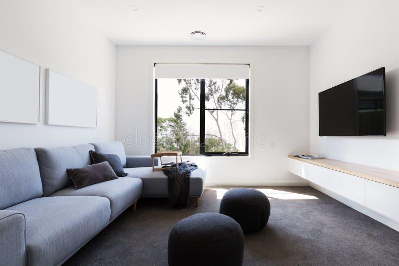 Moderner Lebenfernsehraum in einem zeitgenössischen Haus stockfotos