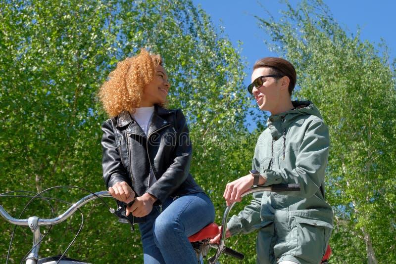Moderner Lebensstil der internationalen Jugend Ein schwarzes Mädchen mit dem angemessenen Haar und ein weißer Kerl in der Sonnenb stockfotografie