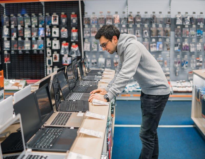 Moderner männlicher Kunde, der Laptop im Computershop wählt stockfoto