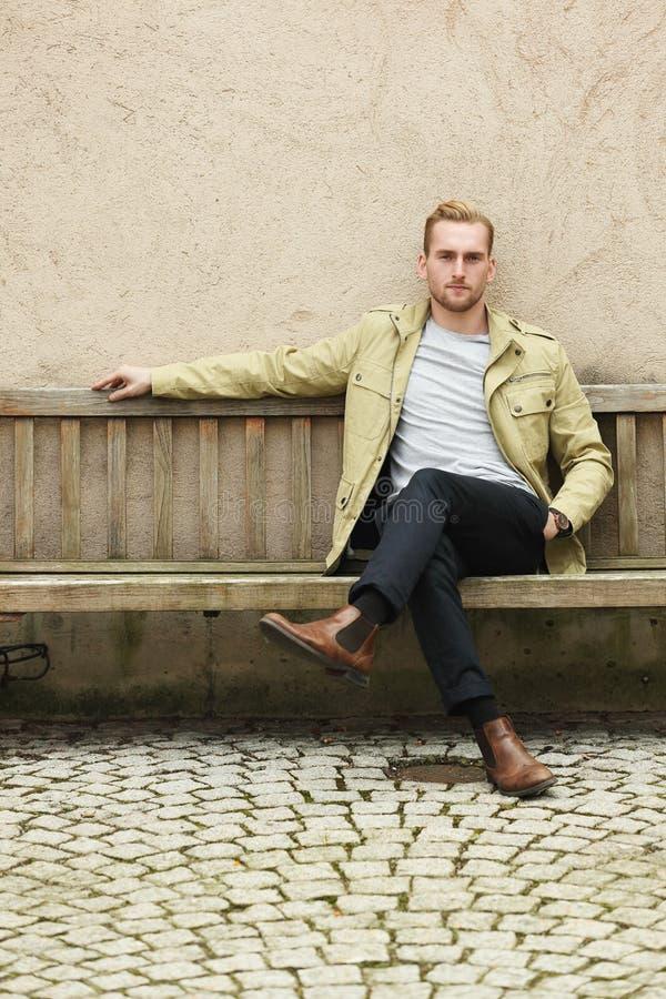 Moderner Mann, der draußen sitzt stockbilder