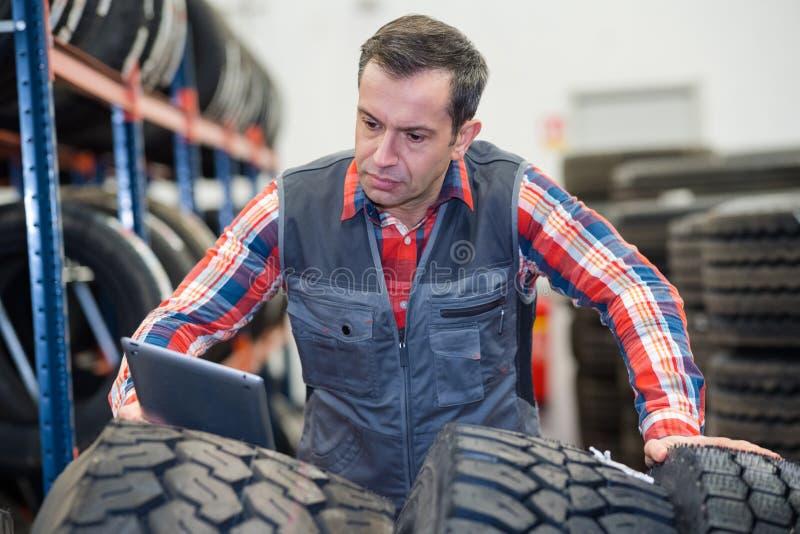 Moderner Mechaniker, der Tablette verwendet, um Reifen zu ?berpr?fen stockfotos