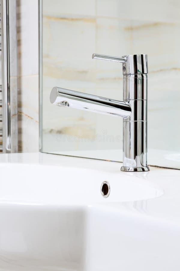 Moderner Metallhahn auf weißem keramischem Waschbecken stockfotografie