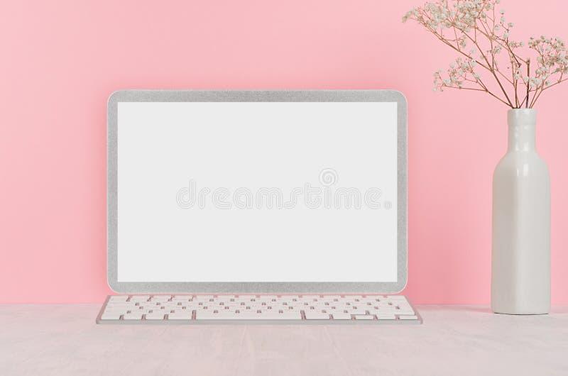 Moderner Modearbeitsplatz - silberner Laptop mit leerem Bildschirm, weißes Briefpapier auf weichem rosa Hintergrund stockfoto