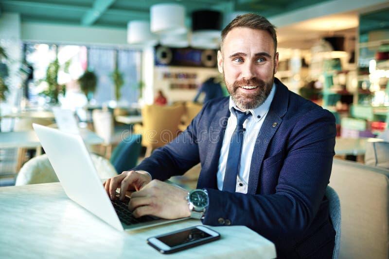 Moderner reifer Geschäftsmann, der im Restaurantaufenthaltsraum arbeitet lizenzfreies stockbild