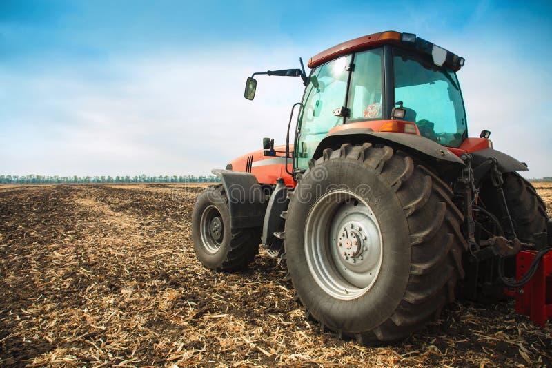 Moderner roter Traktor auf dem Gebiet lizenzfreie stockfotografie