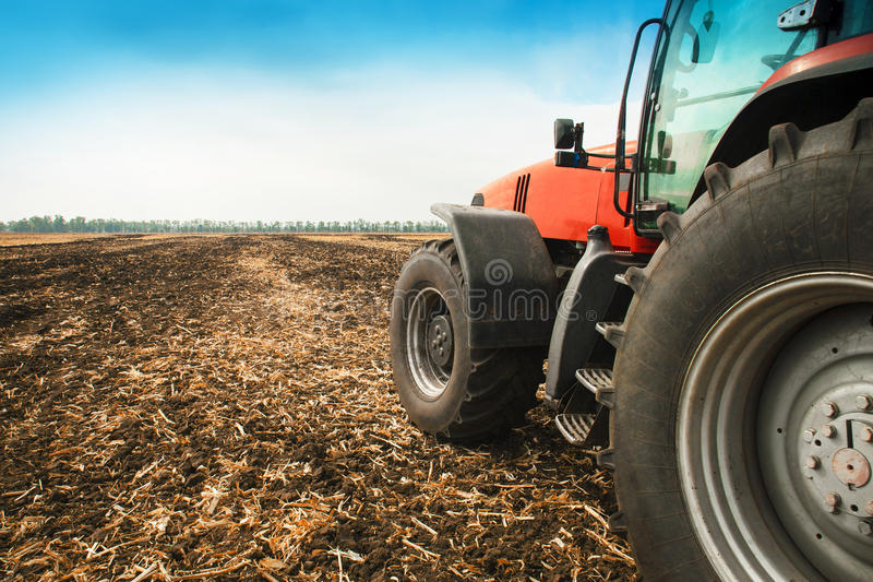 Moderner roter Traktor in der Feldnahaufnahme lizenzfreie stockfotos