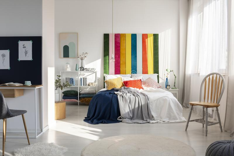Moderner Schlafzimmerinnenraum mit bunter Kopfende, Königgrößenbett, Stuhl und Arbeitsplatz stockfotografie