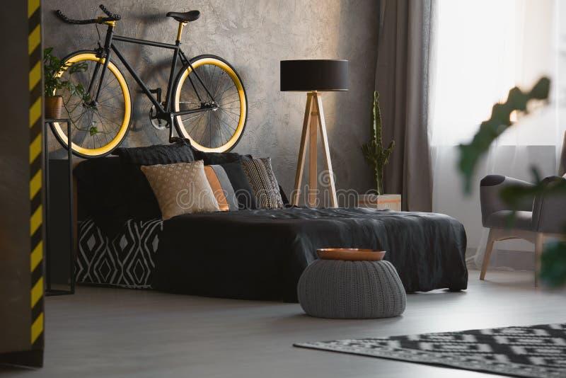 Moderner Schlafzimmerinnenraum mit dekorativen Kissen auf schwarzem Bett, a lizenzfreie stockbilder