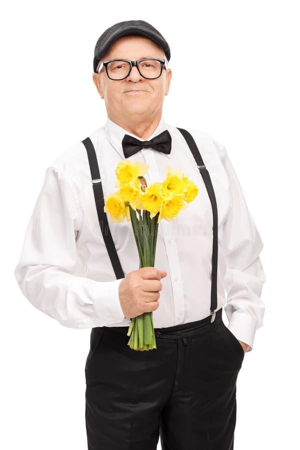 Moderner Senior, der ein Bündel gelbe Tulpen hält lizenzfreie stockfotografie