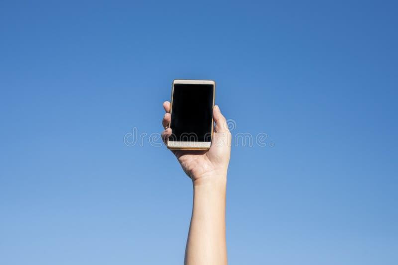 Moderner Smartphone mit leerem Bildschirm Glückliche Menschen, die moderne Handys gegen blauen Himmel zeigen lizenzfreies stockbild