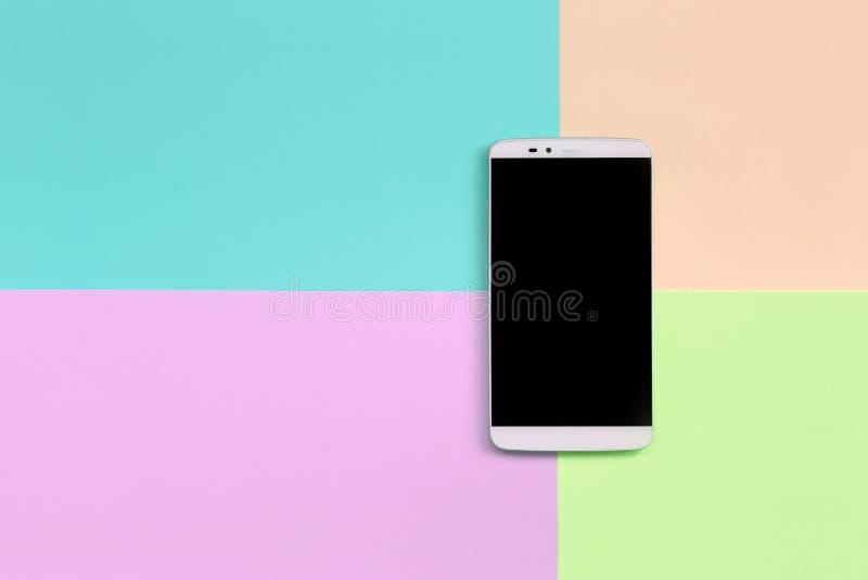 Moderner Smartphone mit schwarzem Schirm auf Beschaffenheitshintergrund von Moderosa, Blauen, korallenroten und Kalkpastellfarben stockfoto