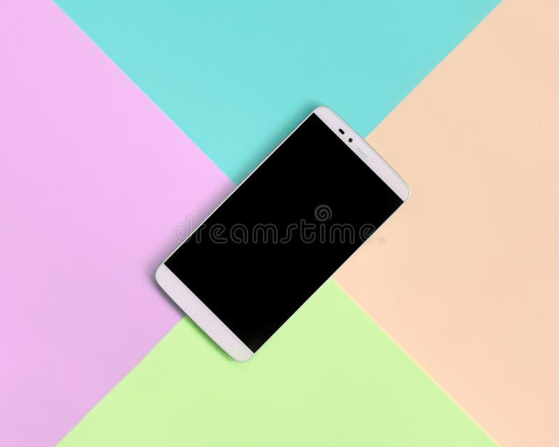 Moderner Smartphone mit schwarzem Schirm auf Beschaffenheitshintergrund von Moderosa, Blauen, korallenroten und Kalkpastellfarben stockfotos