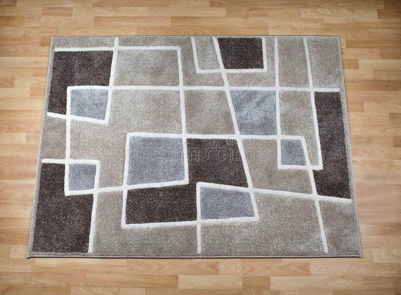 Moderner Teppich auf lamellenförmig angeordnetem Parkettboden lizenzfreies stockfoto