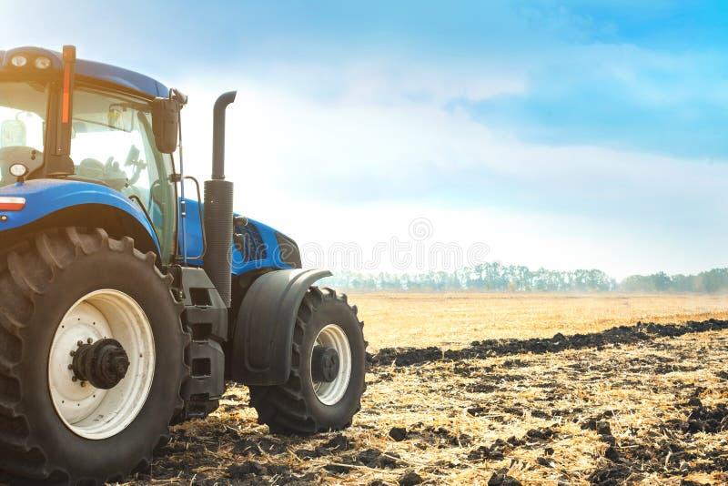 Moderner Traktor, der auf einem Gebiet arbeitet lizenzfreie stockbilder