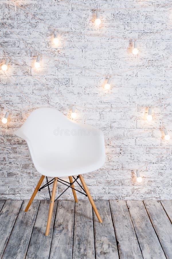 Moderner weißer Plastikstuhl im Dachbodenreinrauminnenraum mit Bretterboden Glühlampegirlande auf weißem Ziegelsteinhintergrund stockbilder