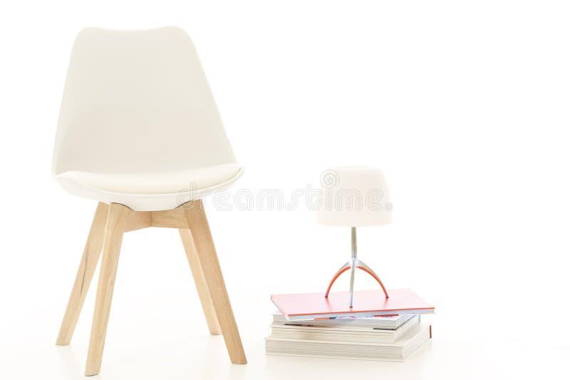 Moderner weißer Stuhl und Lampe im Studio lizenzfreie stockfotos