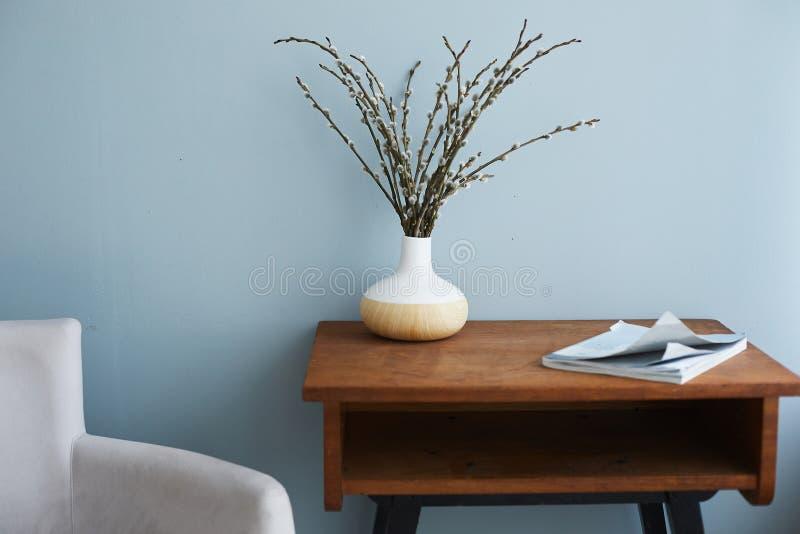 Moderner Wohnzimmerinnenraum, Lehnsessel durch eine Seite und Holztisch mit Vase und Modezeitschrift auf ihr stockbilder