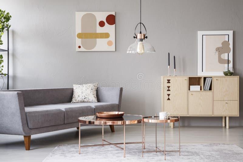 Moderner Wohnzimmerinnenraum mit einem Sofa, kupfernen Couchtischen und einem hölzernen Schrank stockbilder