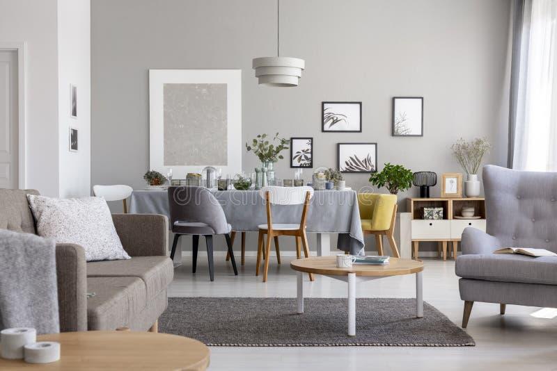 Moderner Wohnzimmerinnenraum mit einem Speisetische und Grafiken auf einer Wand stockbilder