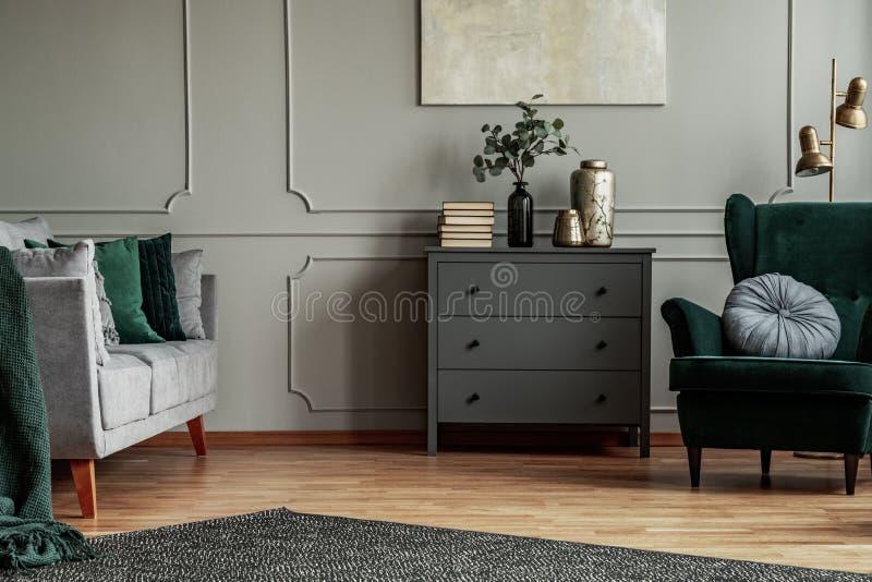 Moderner Wohnzimmerinnenraum mit hölzerner Kommode, skandinavischem Sofa und grünem Smaragdlehnsessel stockfotografie