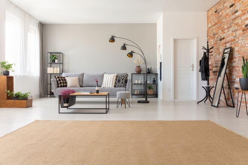 Moderner Wohnzimmerinnenraum mit industriellen Möbeln und Backsteinmauer, wirkliches Foto mit Kopienraum lizenzfreie stockfotos
