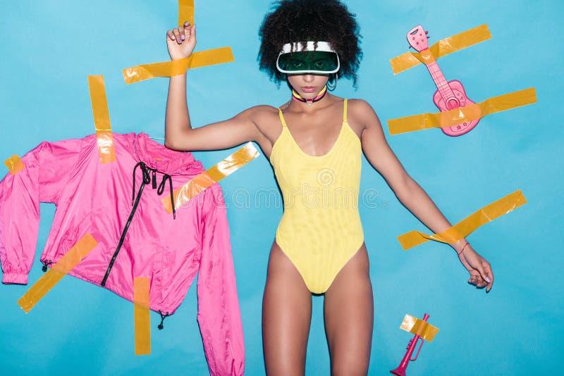 modernes Afroamerikanermädchen im gelben Bodysuit, im rosa Bomber und musikalischen in den Spielwaren geklebt mit schottischem Ba stockbild