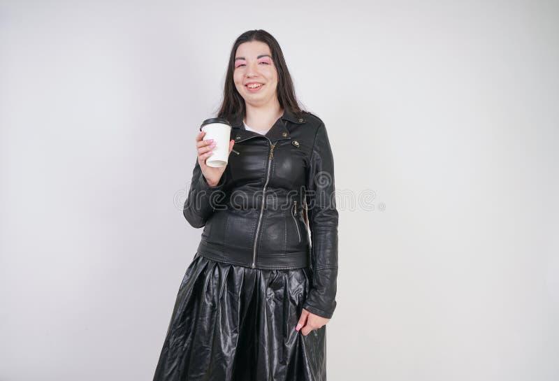 Modernes alternatives M?dchen mit einem Papiertasse kaffee auf einem wei?en Hintergrund im Studio lizenzfreies stockfoto