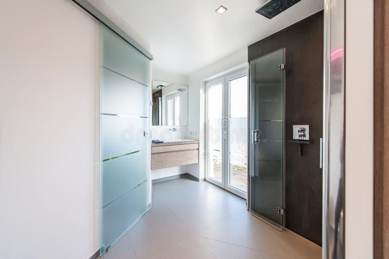 Modernes Badezimmer mit Glastüren und Duschkabine stockbild