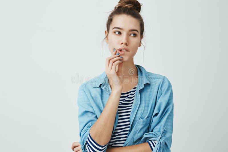 Modernes bezauberndes Mädchen mit der Brötchenfrisur, die beiseite beim Beißen der Lippe und des rührenden Kinns, an konzentriere stockfotos
