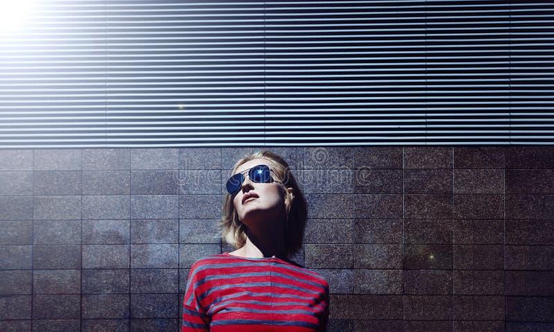 Modernes blondes Mädchen, das in der Sonnenbrille, auf einem Metall gestreiften Hintergrund aufwirft Tag, im Freien Frau gekleide stockfoto