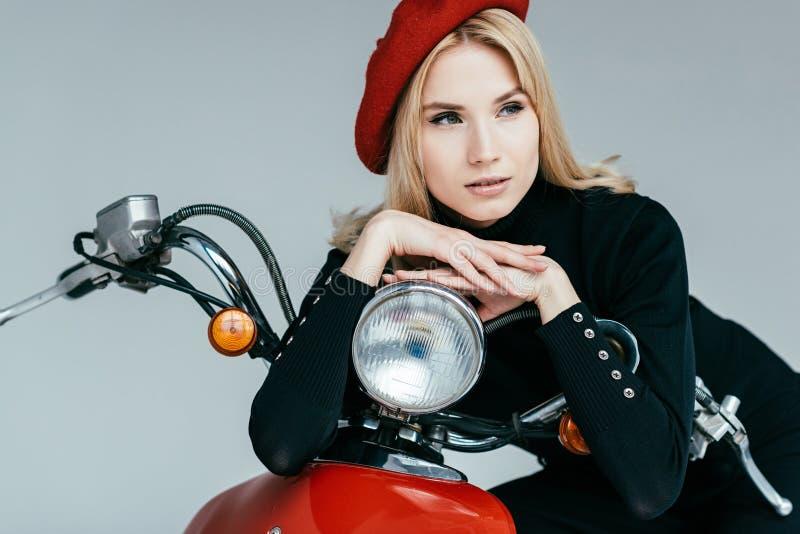 Modernes blondes Mädchen, das roten Roller bereitsteht stockfotografie
