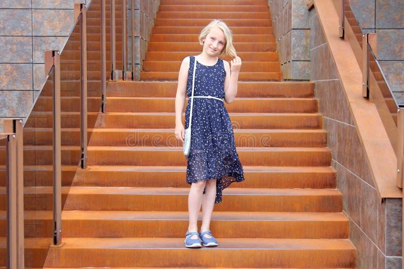 Modernes blondes Mädchen im jugendlichen Alter in einem Kleid, das auf einem stilvollen rostigen Treppenhaus in einem modernen Ge stockfotografie