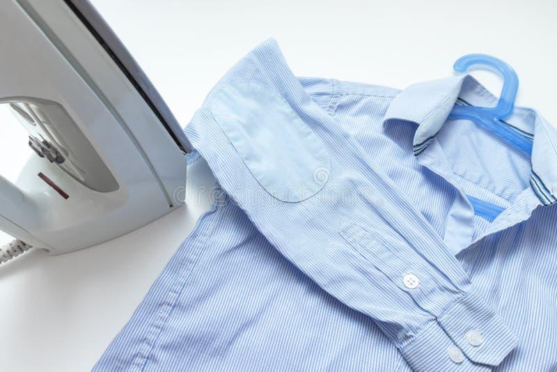 Modernes elektrisches Eisen und ein blaues Hemd auf weißem Hintergrund, Wäscherei und bügelndem Kleidungskonzept stockfotos