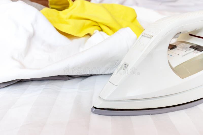 Modernes elektrisches Eisen und ein Haufen der bunten Kleidung auf weißem Textilhintergrund stockbild