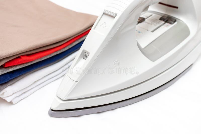 Modernes elektrisches Eisen und ein Stapel der bunten Kleidung auf weißem Hintergrundabschluß oben lizenzfreies stockbild