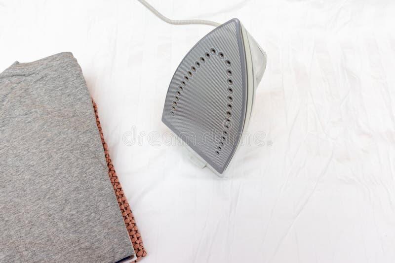 Modernes elektrisches Eisen und ein Stapel von Kleidung auf weißem Hintergrund lizenzfreies stockbild