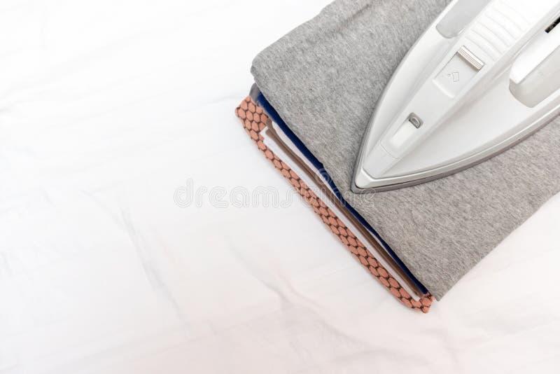 Modernes elektrisches Eisen und ein Stapel von Kleidung auf weißem Hintergrund mit Kopienraum stockbild