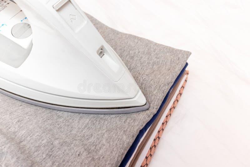 Modernes elektrisches Eisen und ein Stapel von Kleidung auf weißem Hintergrundabschluß oben stockfoto