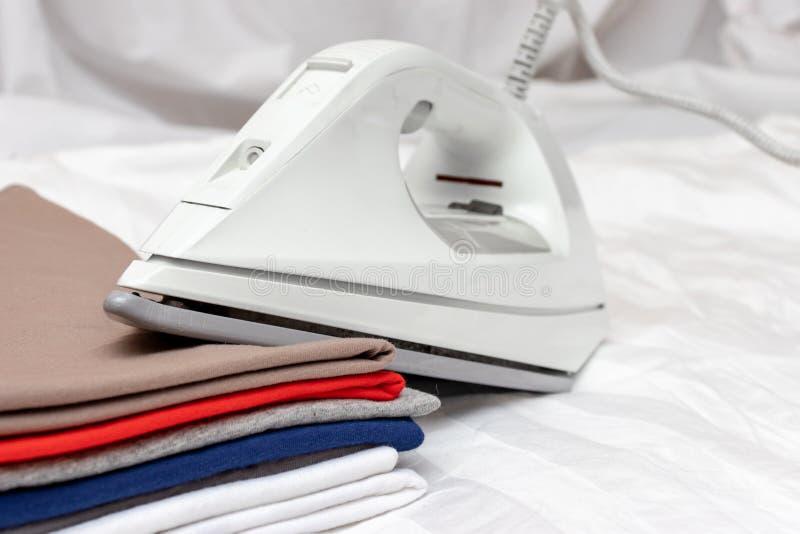 Modernes elektrisches weißes Eisen auf einem Stapel Kleidung schließen oben - Bügeln, Wäscherei und Hausarbeitkonzept stockbild