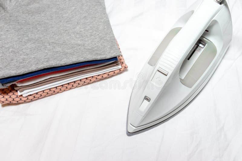 Modernes elektrisches weißes Eisen nahe einem Stapel Kleidung schließen oben - Bügeln, Wäscherei und Hausarbeitkonzept lizenzfreie stockbilder