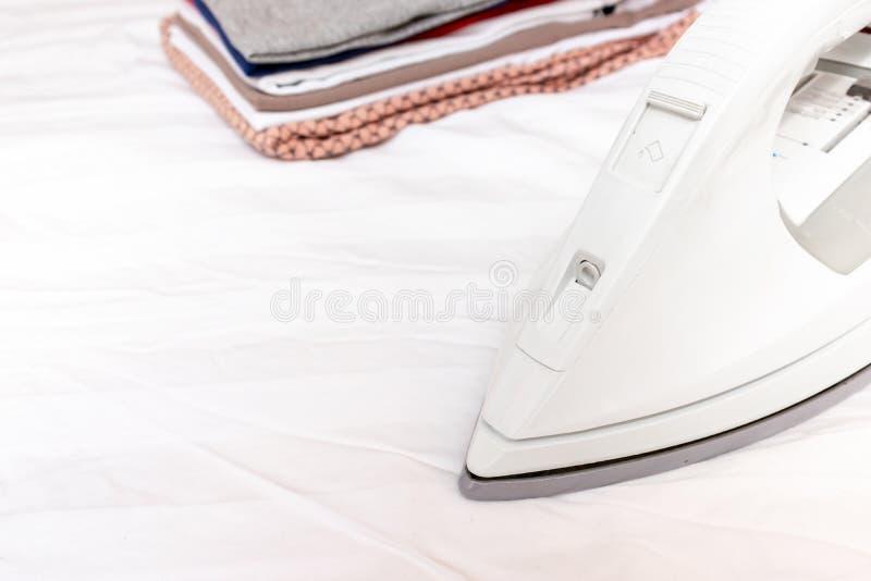 Modernes elektrisches weißes Eisen nahe einem Stapel Kleidung schließen oben mit Kopienraum - Bügeln, Wäscherei und Hausarbeitkon stockbild
