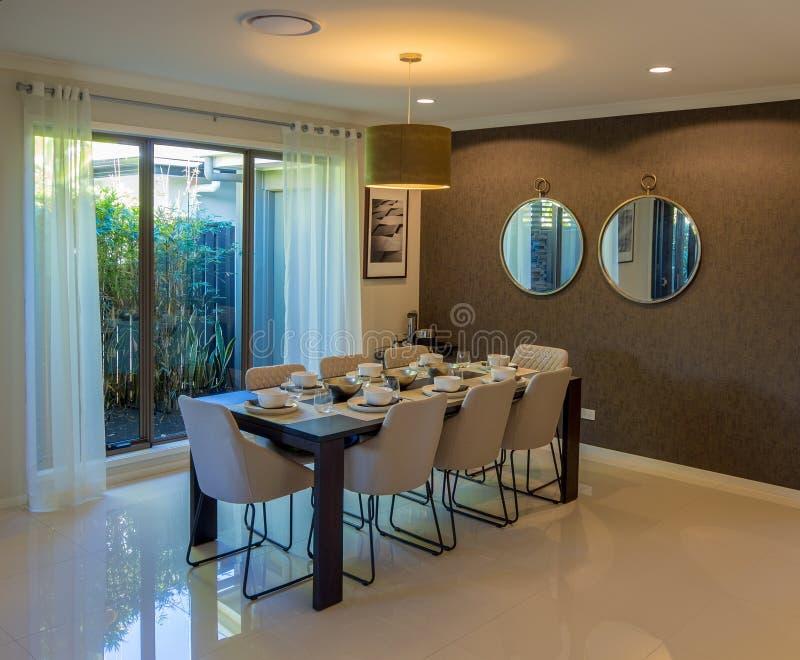 Modernes Esszimmer mit acht Stühlen, die heraus schauen, um im Garten zu arbeiten lizenzfreies stockbild