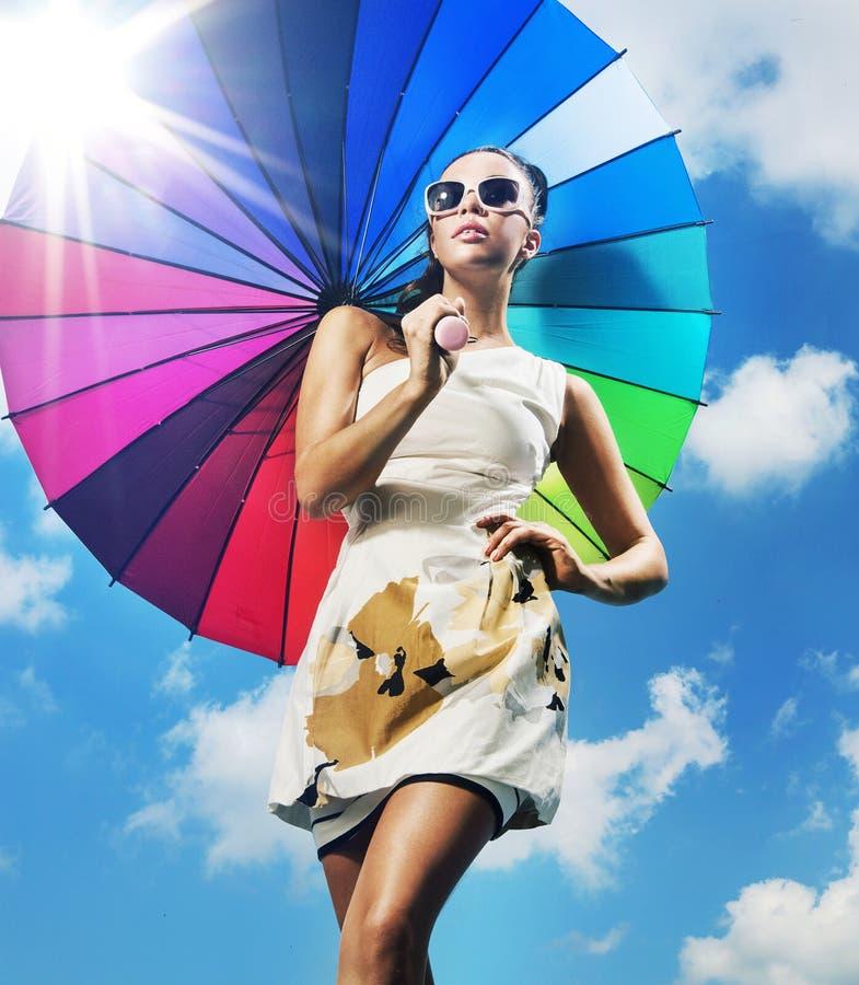 Modernes Foto einer jungen Frau mit einem bunten Regenschirm lizenzfreie stockfotos