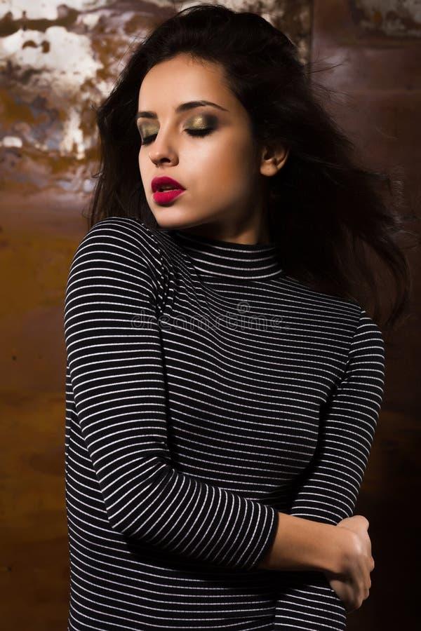 Modernes gebräuntes Brunettemodell mit dem hellen Make-up, das an s aufwirft stockfotos