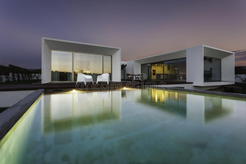Modernes Haus mit GartenSwimmingpool und hölzerner Plattform stockbilder