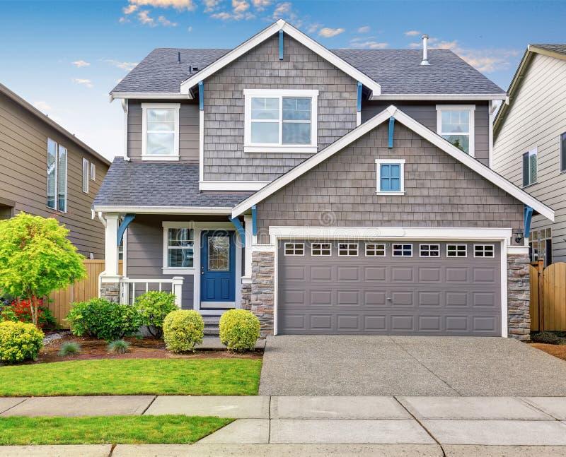 Modernes Haus mit Grauäußerem und blaue weiße Ordnung lizenzfreie stockfotos